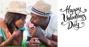 Composite image of happy couple lying in garden together smelling flowers. Happy couple lying in garden together smelling flowers against happy valentines day Stock Photo