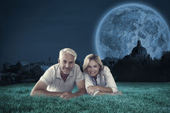 Composite image of happy couple lying smiling at camera Stock Photo
