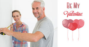 Composite image of happy couple making some measurements together Stock Photo