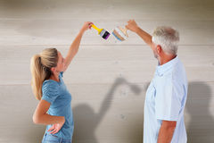 Composite image of happy couple painting wall with paintbrushes Royalty Free Stock Photo