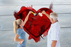 Composite image of happy couple painting wall with paintbrushes Royalty Free Stock Images