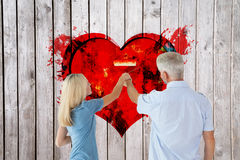 Composite image of happy couple painting wall with roller Royalty Free Stock Photos