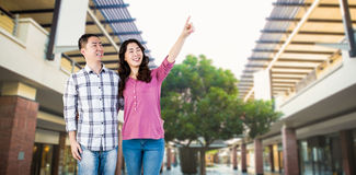 Composite image of happy couple pointing upwards Royalty Free Stock Images