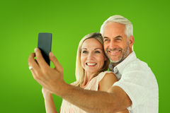 Composite image of happy couple posing for a selfie Royalty Free Stock Photo