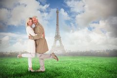 Composite image of happy couple posing in trench coats Royalty Free Stock Photography