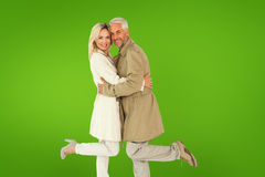 Composite image of happy couple posing in trench coats Stock Photos