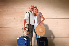 Composite image of happy couple ready to go on holiday Stock Photography