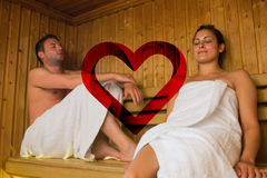 Composite image of happy couple relaxing in a sauna. Happy couple relaxing in a sauna against heart stock image