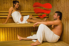 Composite image of happy couple relaxing in a sauna and chatting Stock Images