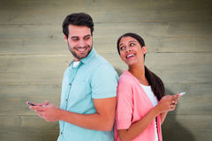 Composite image of happy couple sending text messages Royalty Free Stock Photography