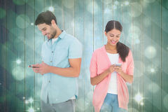 Composite image of happy couple sending text messages Stock Images