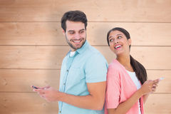 Composite image of happy couple sending text messages Stock Photo
