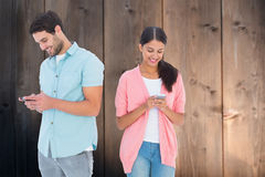 Composite image of happy couple sending text messages Stock Photos
