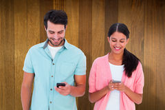 Composite image of happy couple sending text messages Royalty Free Stock Images