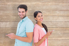 Composite image of happy couple sending text messages Royalty Free Stock Photo