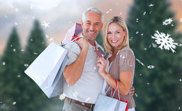 Composite image of happy couple with shopping bags and credit card Royalty Free Stock Image