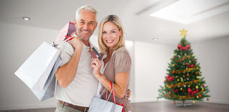 Composite image of happy couple with shopping bags and credit card Stock Photography