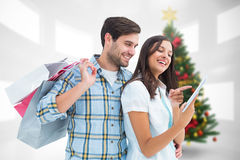 Composite image of happy couple with shopping bags and tablet Stock Images
