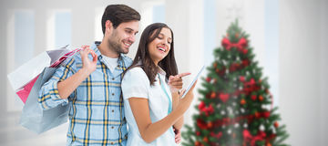 Composite image of happy couple with shopping bags and tablet Royalty Free Stock Photos