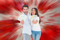 Composite image of happy couple showing their money Stock Photography