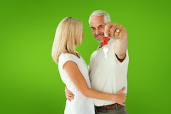 Composite image of happy couple showing their new house key Royalty Free Stock Photos