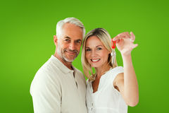 Composite image of happy couple showing their new house key. Happy couple showing their new house key against green vignette Royalty Free Stock Photography
