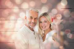 Composite image of happy couple showing their new house key Royalty Free Stock Image