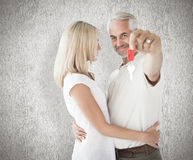Composite image of happy couple showing their new house key Stock Images