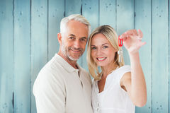 Composite image of happy couple showing their new house key. Happy couple showing their new house key against wooden planks Royalty Free Stock Images