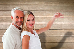 Composite image of happy couple showing their new house key Royalty Free Stock Images