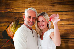 Composite image of happy couple showing their new house key Royalty Free Stock Photo