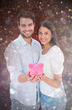 Composite image of happy couple showing their piggy bank Royalty Free Stock Images