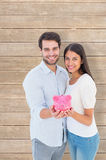 Composite image of happy couple showing their piggy bank Stock Photography