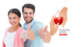 Composite image of happy couple showing thumbs up. Happy couple showing thumbs up against blood donation Stock Photo