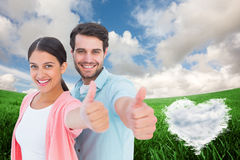 Composite image of happy couple showing thumbs up. Happy couple showing thumbs up against cloud heart Stock Photography
