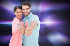Composite image of happy couple showing thumbs up. Happy couple showing thumbs up against digitally generated cool nightlife design Royalty Free Stock Image