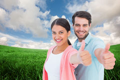 Composite image of happy couple showing thumbs up. Happy couple showing thumbs up against green field under blue sky Stock Image