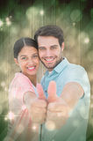 Composite image of happy couple showing thumbs up. Happy couple showing thumbs up against light design shimmering on green Stock Photos