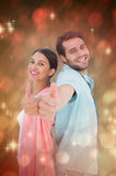Composite image of happy couple showing thumbs up. Happy couple showing thumbs up against light design shimmering on red Stock Image