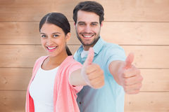 Composite image of happy couple showing thumbs up. Happy couple showing thumbs up against overhead of wooden planks Royalty Free Stock Photography