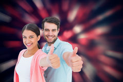 Composite image of happy couple showing thumbs up. Happy couple showing thumbs up against valentines heart pattern Stock Photo