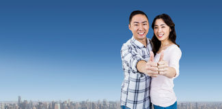 Composite image of happy couple showing thumbs up against white background. Happy couple showing thumbs up against white background against cityscape Stock Images
