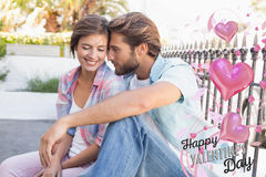 Composite image of happy couple sitting and cuddling. Happy couple sitting and cuddling against happy valentines day royalty free stock image