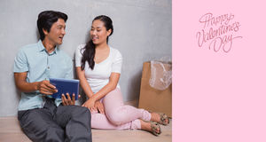 Composite image of happy couple sitting on floor using tablet surrounded by boxes Stock Photos