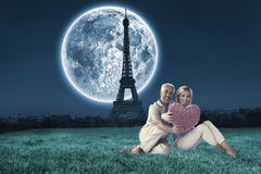 Composite image of happy couple sitting and holding heart pillow. Happy couple sitting and holding heart pillow against large moon over paris stock photo
