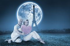 Composite image of happy couple sitting and holding heart pillow Royalty Free Stock Photo