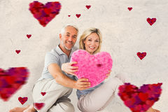 Composite image of happy couple sitting and holding heart pillow. Happy couple sitting and holding heart pillow against parchment royalty free stock image