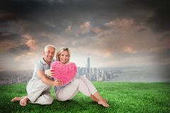 Composite image of happy couple sitting and holding heart pillow Stock Photography