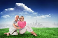 Composite image of happy couple sitting and holding heart pillow Royalty Free Stock Photography