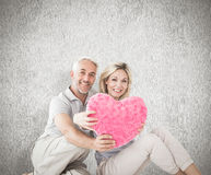 Composite image of happy couple sitting and holding heart pillow Royalty Free Stock Image